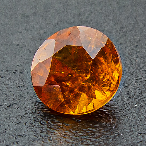 Mandarine Garnet from Namibia. 0.16 Carat. Round, very distinct inclusions