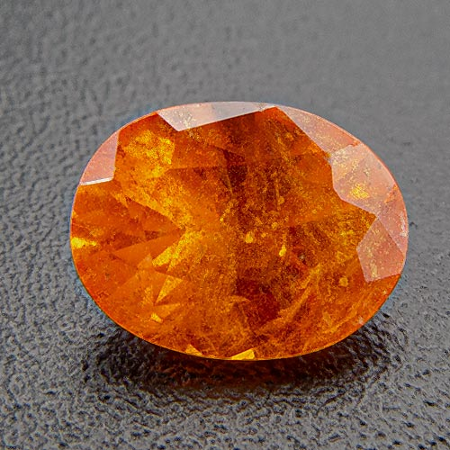 Mandarin Garnet from Namibia. 0.63 Carat. Oval, very distinct inclusions
