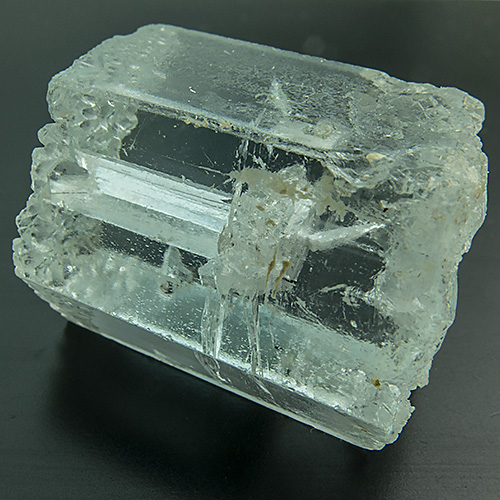 "Aquamarine With Negative Tourmaline from Pakistan. 1 Piece. large aquamarine crystal with etch figures at both ends. the hydrofluoric acid causing these figures also etched an included, large tourmaline crystal out of the aquamarine. the result is a surface-reaching ""negative crystal"", a cavity in the shape of the tourmaline crystal which even shows the tourmalines typical striations!"
